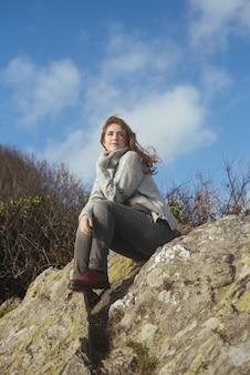 Вертикальный снимок улыбающейся женщины, сидящей на берегу с деревьями