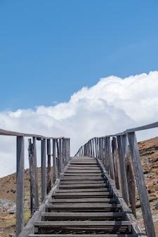 エクアドルのガラパゴス諸島の空に触れる山々に通じる階段の垂直ショット