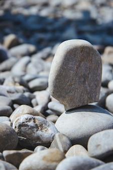낮 동안 다른 사람과 균형을 이루는 돌의 수직 샷