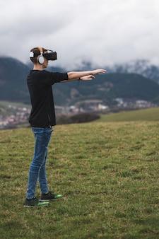 Вертикальный снимок мужчины-подростка, использующего виртуальную реальность и забывающего