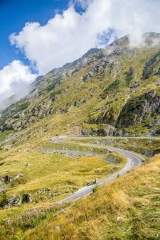 岩が多い緑の山々に続くトレイルの垂直ショット