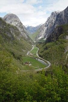 녹색 들판이 있는 산을 가로지르는 트레일의 세로 샷