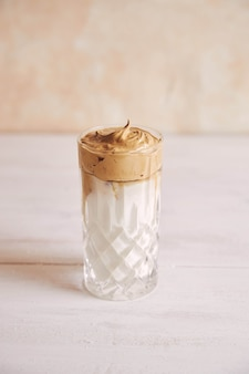 白い木のテーブルの上に牛乳とトレンディなおいしい新鮮なダルゴナコーヒーの垂直ショット