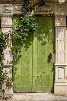 木製の緑のドアのユニークなデザインの垂直ショット