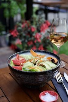 Вертикальный снимок вегетарианского салата с авокадо, помидорами и орехами на столе с напитком на нем