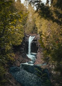 Вертикальный выстрел водопад течет вниз по течению возле скал и растений
