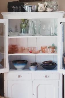 さまざまな種類のセラミックとガラスの台所用品が入った白い棚の垂直方向のショット