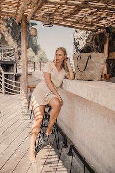 Вертикальный снимок женщины, сидящей возле барной стойки в дневное время