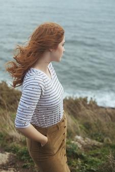 海と海岸に立っている女性の垂直ショット