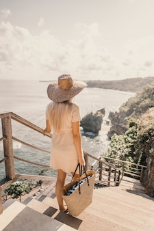 해변 옆에 핸드백을 들고 계단을 내려가는 여자의 세로 샷