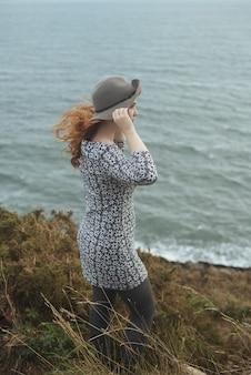 바다와 모자를 쓰고 여자의 세로 샷