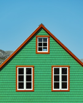 맑고 푸른 하늘 아래 나무 그린 하우스의 세로 샷