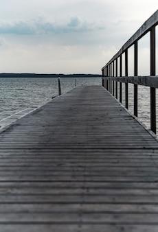 曇り空の下で美しい参照のcpastで木製の桟橋の垂直ショット
