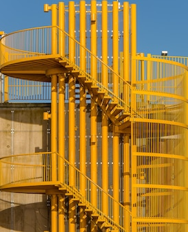햇빛 아래 노란색 나선형 계단의 수직 샷