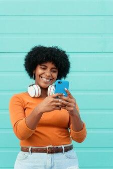 Вертикальный снимок молодой привлекательной дамы в наушниках, использующей свой телефон