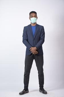 양복과 안면 마스크를 쓴 젊은 흑인 사업가가 자신 있게 서 있는 세로 사진