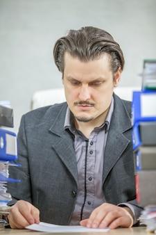 彼のオフィスで働いている青年実業家の垂直ショット-ハードワークの概念