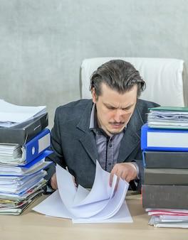 그의 사무실에서 일하는 젊은 사업가의 세로 샷-노력의 개념