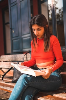 ベンチ公園で本を読んで赤いスタイリッシュなブラウスで若い白人ブルネットの垂直ショット