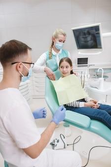 Вертикальный снимок молодой девушки, проходящей стоматологическое обследование в клинике