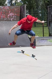 公園でスケートボードでトリックをしている若い男性の垂直ショット