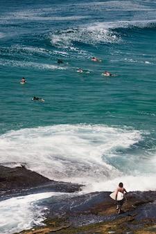 サーフィンのために海に入る若い男性の垂直ショット