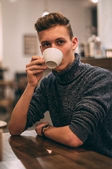 カフェでコーヒーを飲む若い男の縦のショット