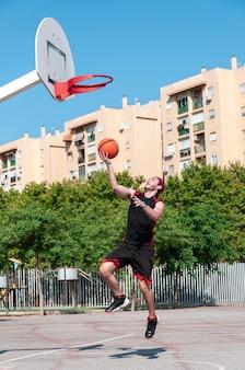 농구 바구니에 공을 던지는 젊은 남자의 세로 샷