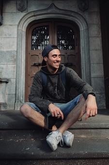 バックパックで古いドアに座っている若い南アメリカ人の垂直ショット