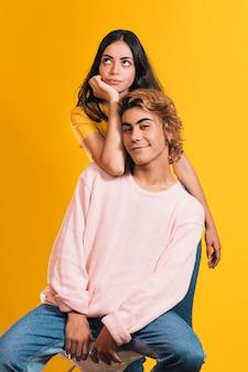明るい黄色の背景に対してポーズをとる若いスタイリッシュなカップルの垂直ショット