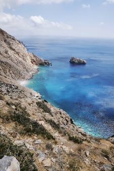青い空の下でギリシャ、アモルゴス島のアギアアンナの垂直ショット