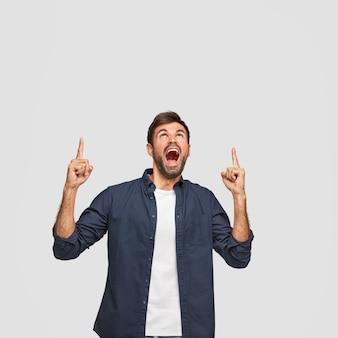 Вертикальный снимок изумленного парня с широко открытым ртом, показывает указательными пальцами вверх