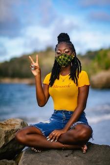 Vサインを身振りで示す緑のフェイスマスクでアフリカ系アメリカ人の女性の垂直ショット