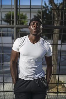 フェンスに寄りかかって白いシャツを着たアフリカ系アメリカ人男性の垂直ショット