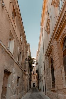 昼間の青空の下で建物の真ん中にある路地の垂直ショット
