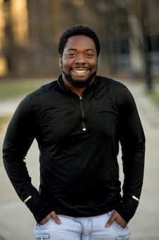 カメラに向かって笑みを浮かべて魅力的なアフリカ系アメリカ人男性の垂直ショット