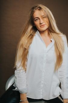 Вертикальный снимок привлекательной блондинки, позирующей сидя на табурете