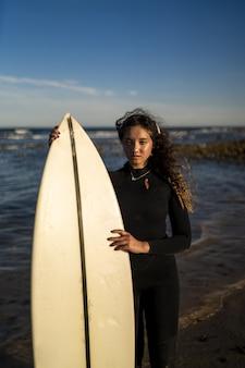 スペインの海岸でサーフボードを保持している魅力的な女性の垂直ショット