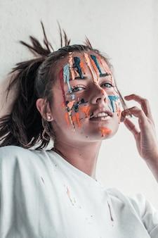 彼女の顔に異なる色のペンキを塗った魅力的な女性の垂直ショット