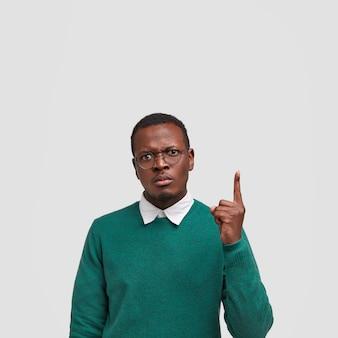 Вертикальный снимок сердитого недовольного мужчины с черной кожей, угрюмым лицом, указывает указательным пальцем вверх, одетого в повседневный свитер