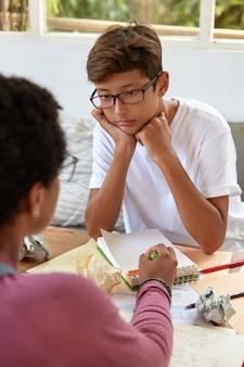 Вертикальный снимок азиатского стажера в очках и белой футболке