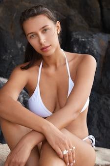매력적인 여성 관광객의 세로 샷은 멋진 몸매를 가지고 있습니다.