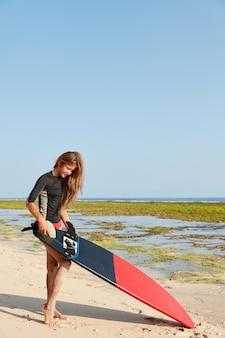 水着姿の魅力的な女性の垂直ショット、サーフボーダーを保持し、サーフィンのための亜鉛を保持します