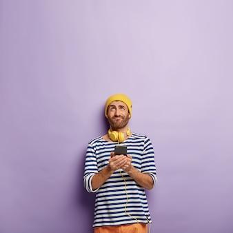 Вертикальный снимок привлекательного молодого мужчины, держащего современный сотовый телефон, сфокусированного вверх, слушающего любимую композицию в стереонаушниках, см. выше