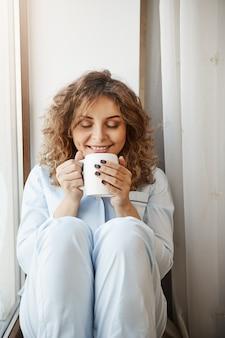 Вертикальный снимок красивой кавказской молодой женщины с вьющимися волосами, сидя на подоконнике, держа чашку вкусного кофе, нюхая его довольной и расслабленной улыбкой, имея прекрасное утро в одиночестве