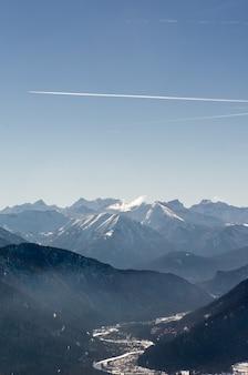 エンジントレイルのある明るい空の下の美しい山脈の垂直ショット