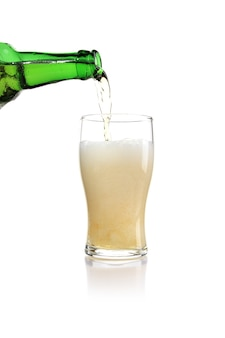 ガラスに注がれた緑色のボトルからのビールの垂直ショット