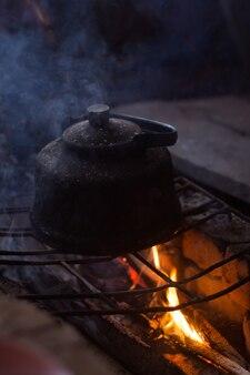 キャンプファイヤーの上で沸騰する黒いスモークケトルの垂直ショット