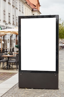 屋外のカフェテリアの近くの街の背景に対してpavemenetに立っている空白の看板の垂直ショット