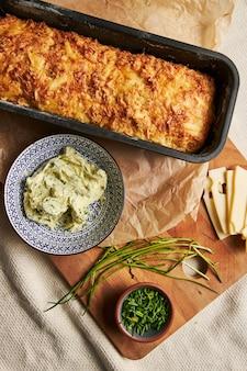 Вертикальный снимок хлеба с сырным травяным маслом на дереве